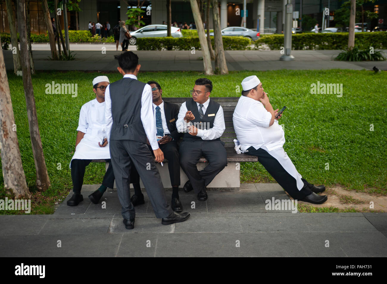 13.07.2018, Singapore, Republic of Singapore, Asia - A group of hotel employees is seen taking a short break on a bench in Marina Bay. - Stock Image