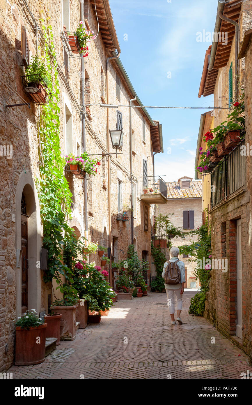 A Lady tourist strolling in one of the adjoining ways of the main street of Pienza (Tuscany - Italy). - Stock Image