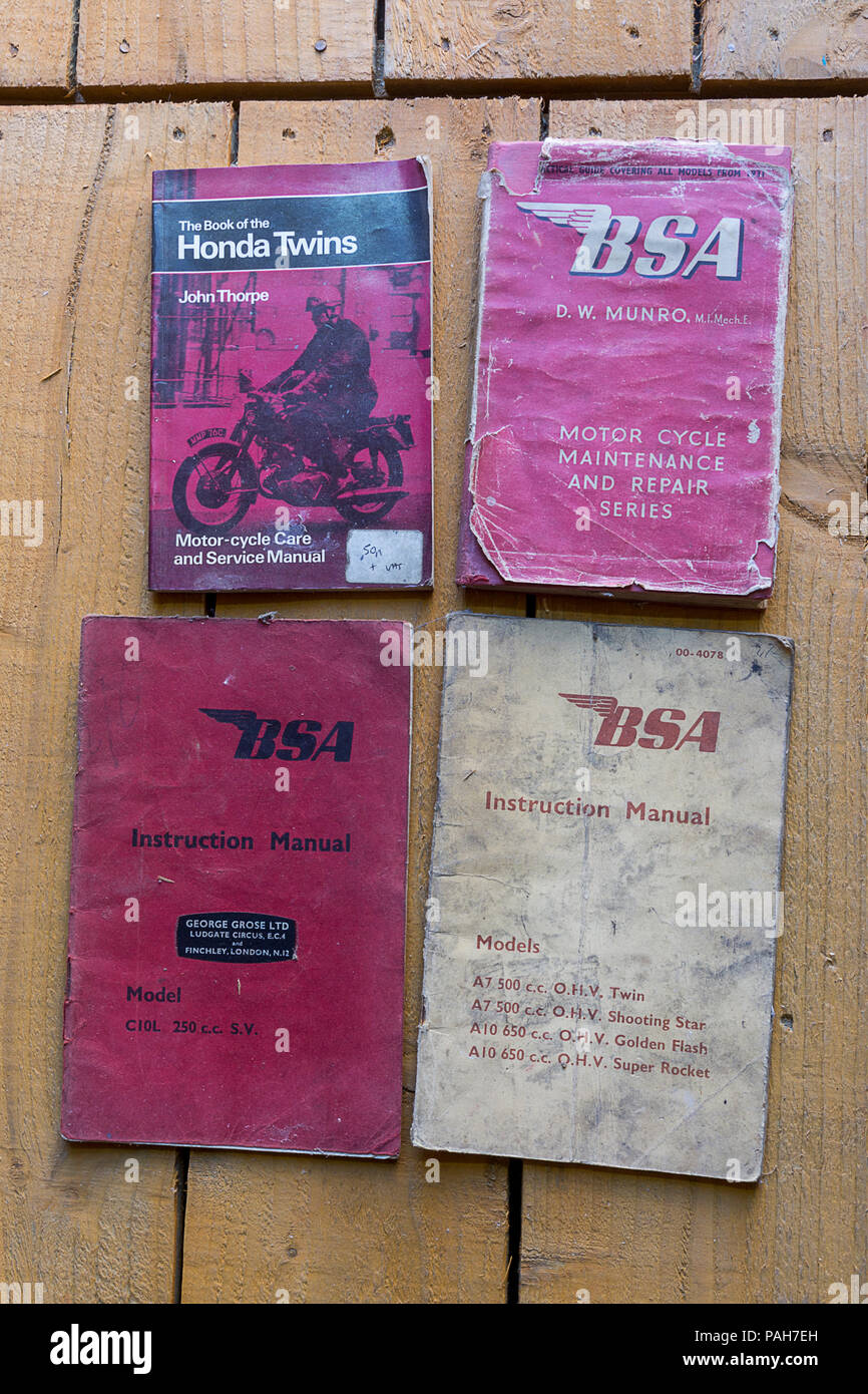 BSA and Honda old manuals on my shed floor from 1931 with side valve and ohv models illustrated BSA (British small arms) 500cc and 650cc ohv twins. - Stock Image