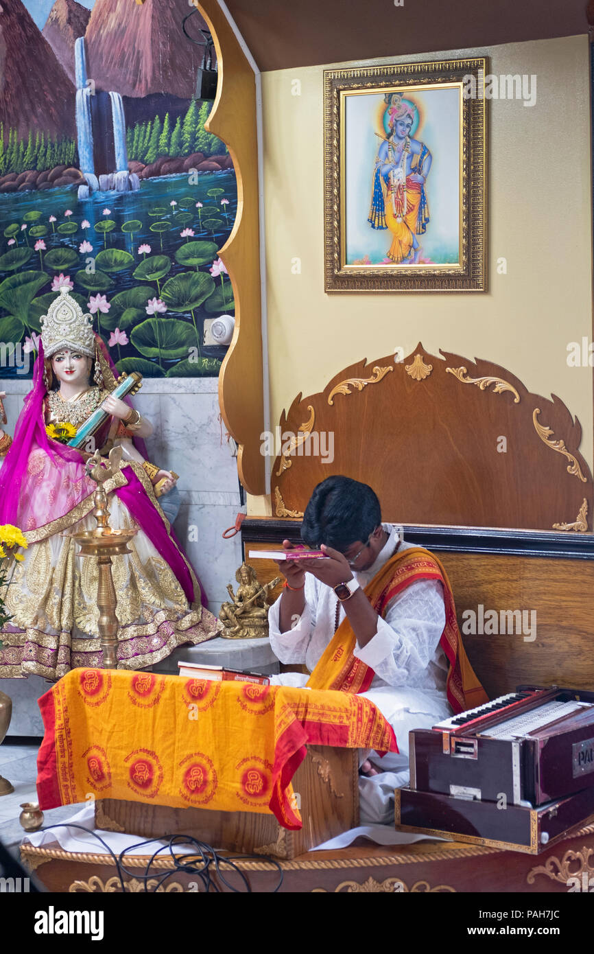 A teenage pandit holding a copy of the Bhagavad Gita while leading a youth service at the Milan Mandir Hindu temple in South Ozone Park, Queens, NYC. - Stock Image