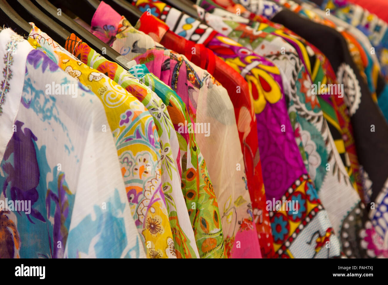 68a4e37918 Brightly coloured clothes in a Greek clothes shop - Stock Image