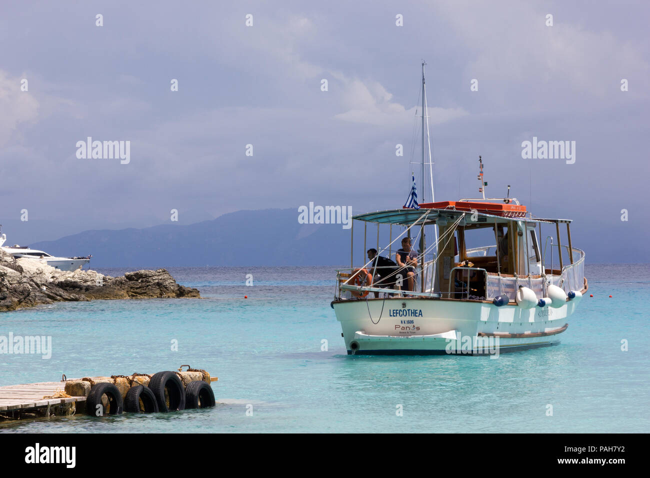 A small passenger ferry is moored up on the island of Antipaxos, Greece - Stock Image