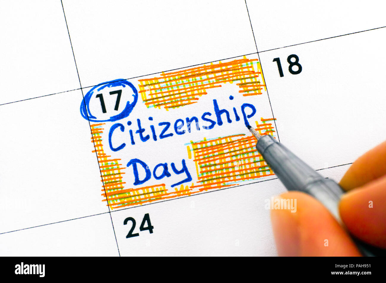 Person fingers with pen writing reminder Citizenship Day in calendar. Close-up. - Stock Image