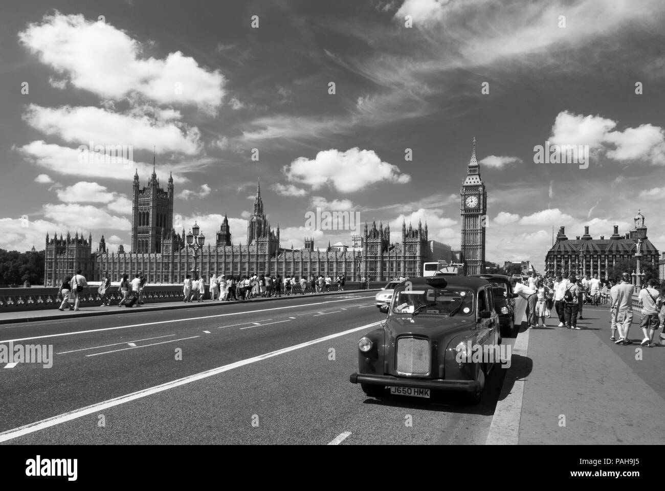 A black and white image of a London taxi cab stopped on Westminster bridge as tourists make their way to the Houses of Parliament and Big Ben - Stock Image
