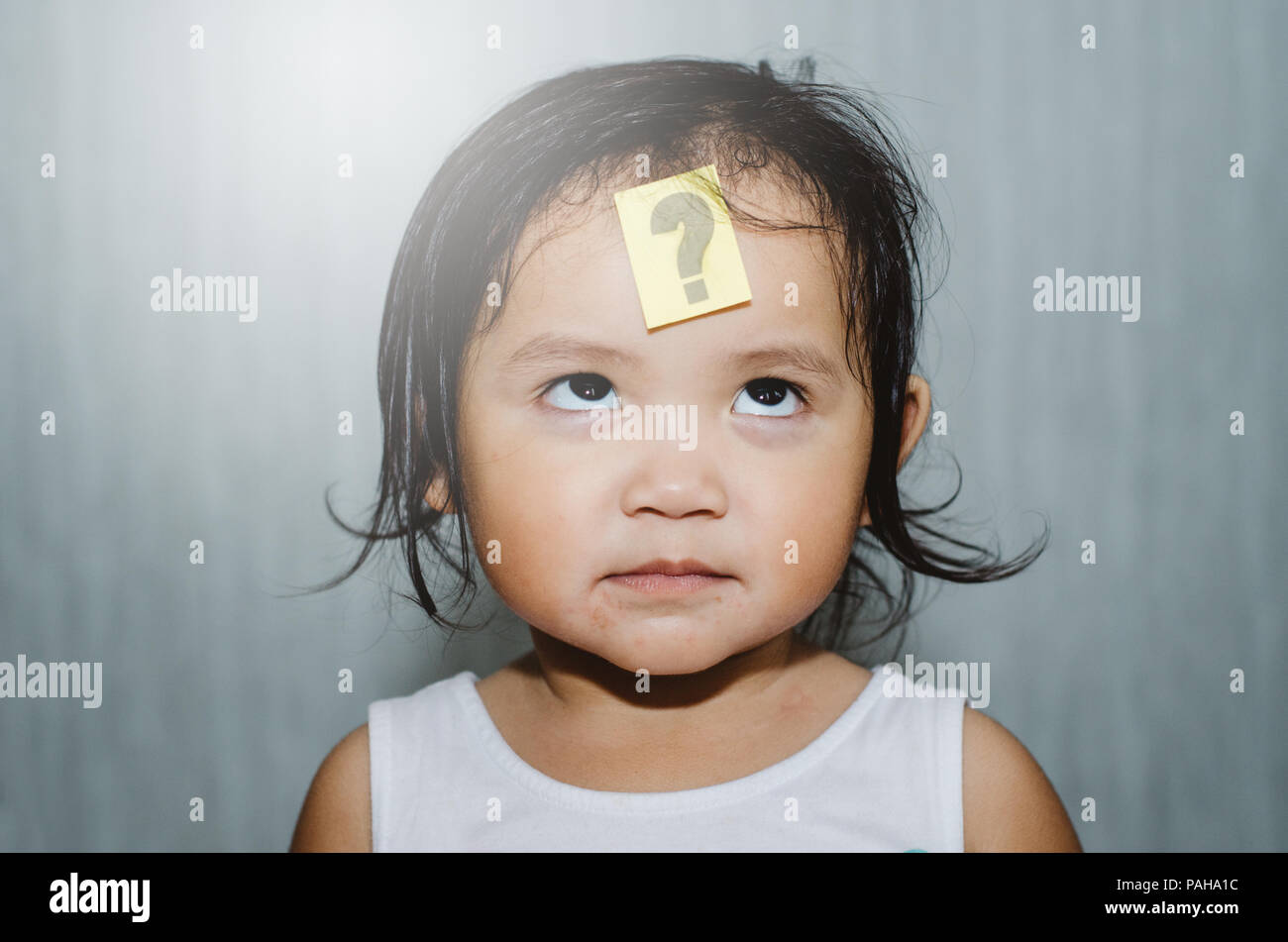 asian cute toddler looking at question mark on her forehead with funny face. child learning and growth concept - Stock Image