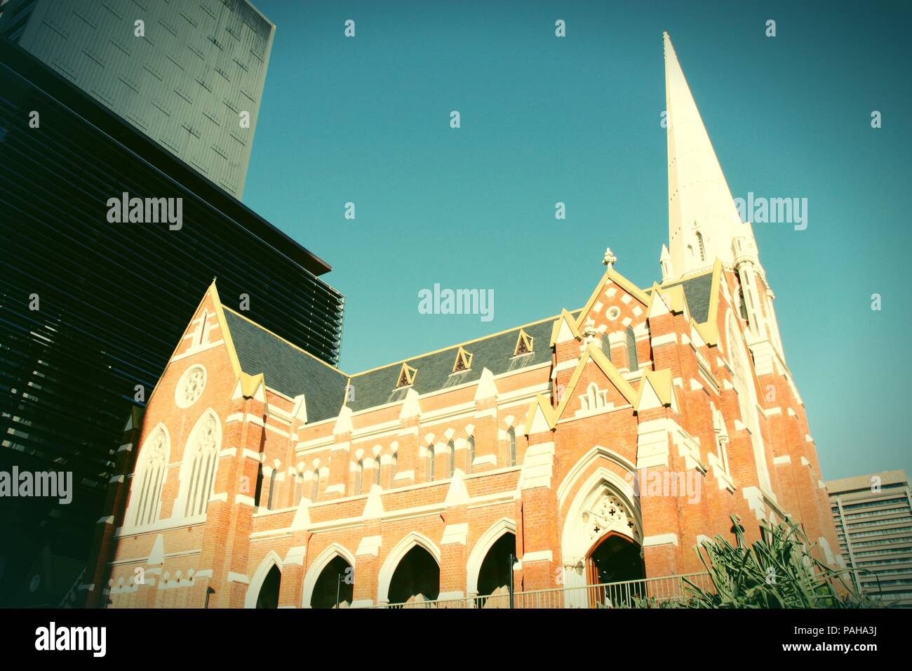 Albert Street Uniting Church surrounded by skyscrapers in Brisbane, Queensland, Australia. Cross processed retro color style. - Stock Image