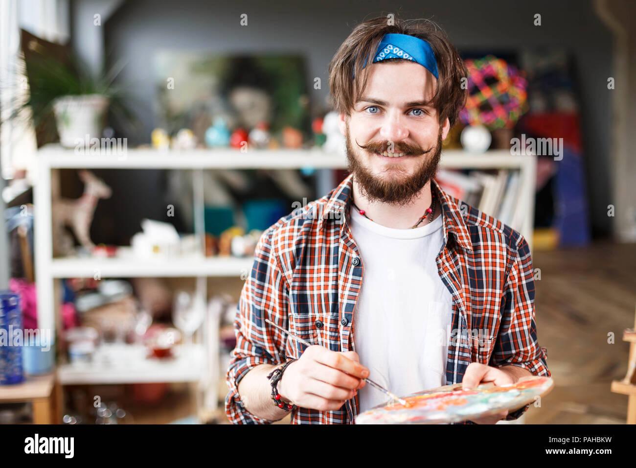 caucasian dark haired bearded hipster male artist in blue bandana