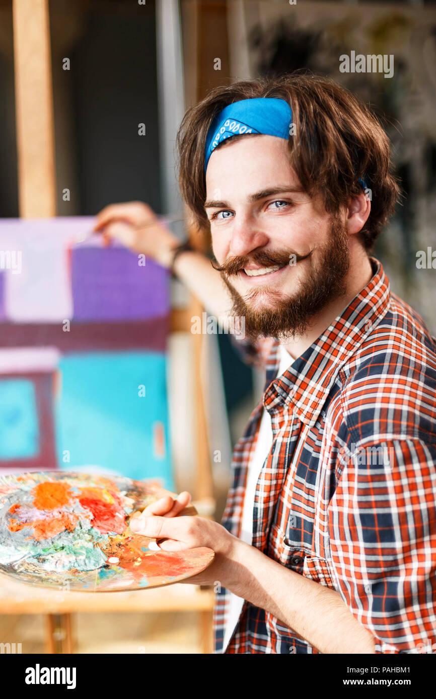 handsome dark haired bearded hipster male artist in blue bandana