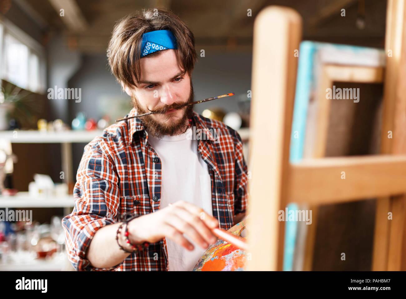 creative dark haired bearded hipster male artist in blue bandana