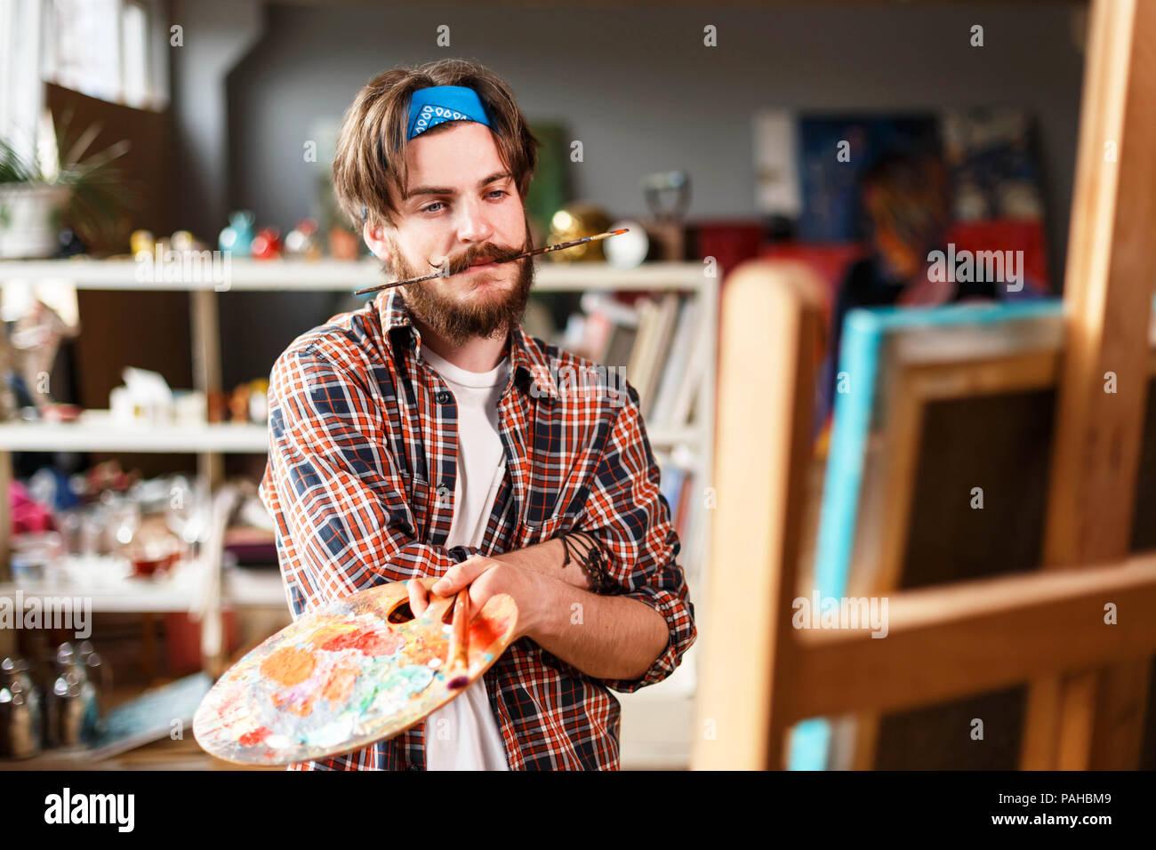 dark haired bearded hipster male artist in blue bandana holding