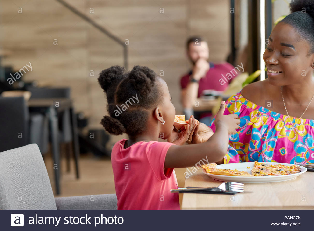 Happy mother feeding child delicious pizza sitting in local restaurant. Smiling, having good mood, wonderful time together, lovely family. Other clients sitting in cafe's background. Loft interior. - Stock Image