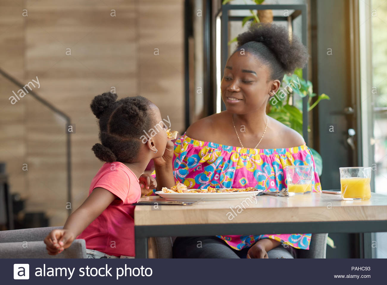 Smiling mother feeding child delicious pizza sitting in local cafe. Happy, having good mood, wonderful time together, lovely family. Other clients sitting in cafe's background. Loft interior. - Stock Image