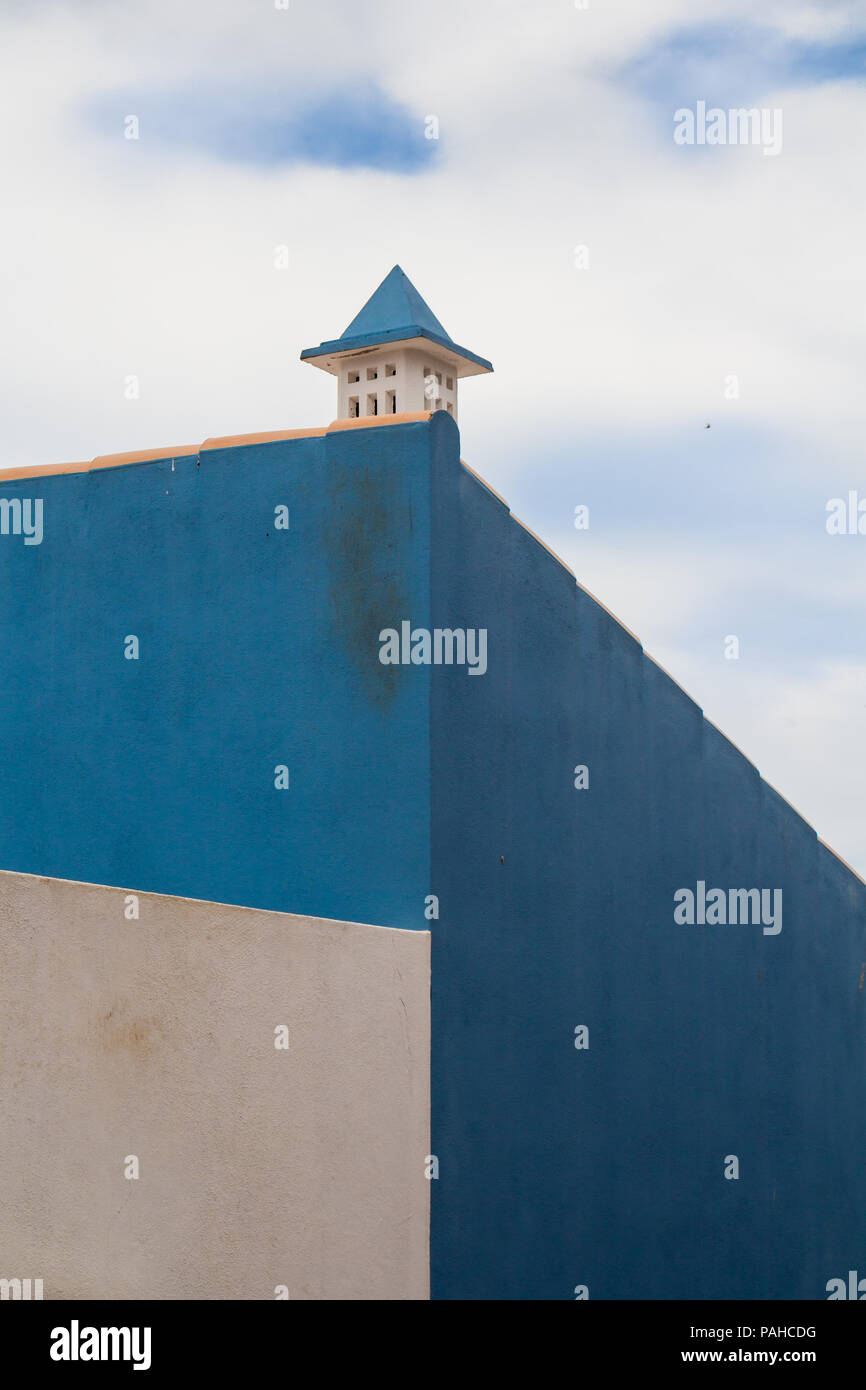 Side wall of a house painted white and two tones of blue. Traditional portuguese chimney. Cloudy sky matching with the facade. Lagos, Algarve, Portuga - Stock Image