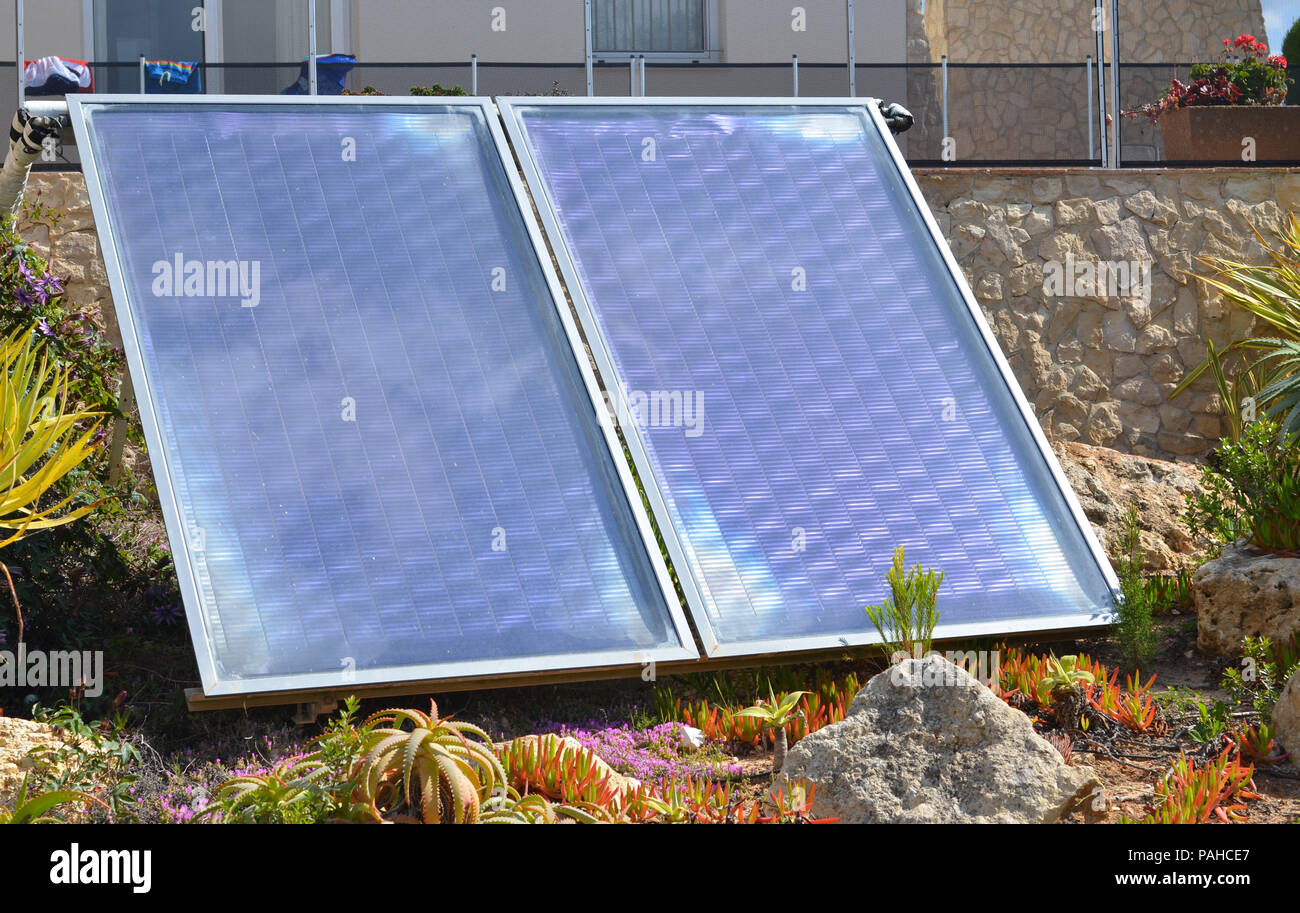 Domestic solar panels in a garden - Stock Image