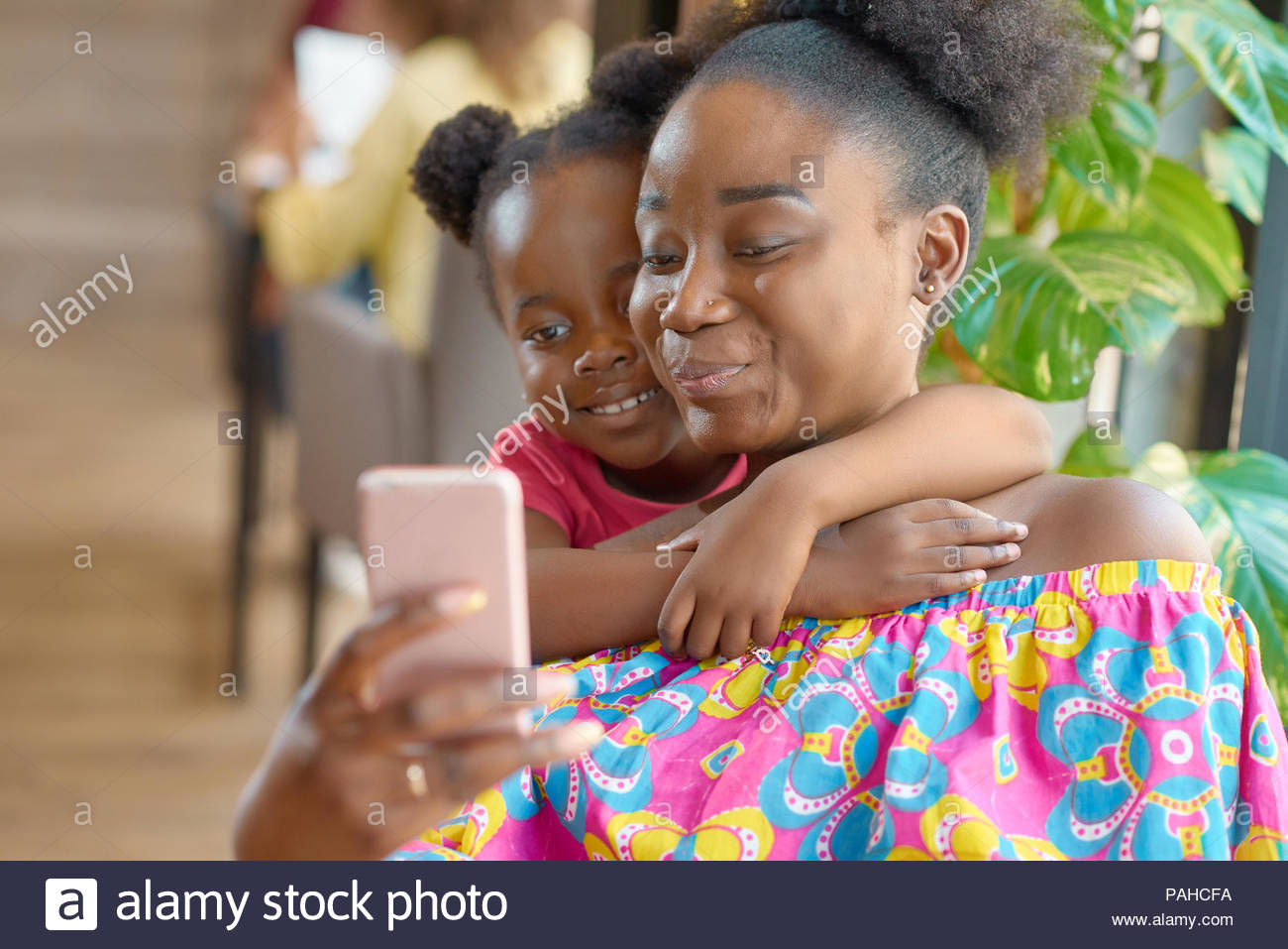 Smiling mother taking selfie with her cute little daughter. Looking at smartphone, feeling happy, satisfied, relaxed. Family hugs, lovely photo. Having good time. Sitting in cafe. - Stock Image