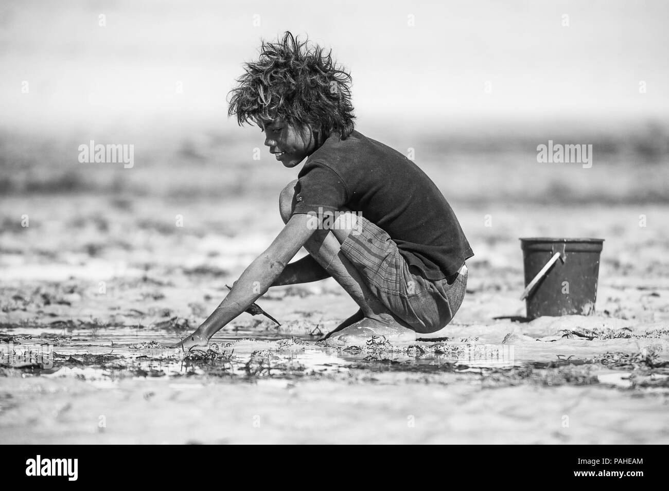 ANTANANARIVO, MADAGASCAR - JULY 3, 2011: Unidentified Madagascar boy plays with sand. People in Madagascar suffer of poverty due to slow development o - Stock Image