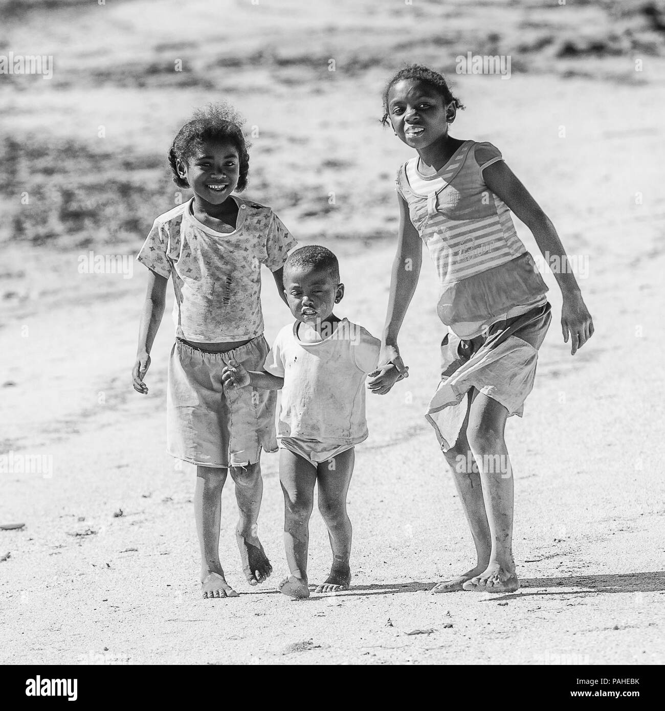 ANTANANARIVO, MADAGASCAR - JULY 3, 2011: Unidentified Madagascar beautiful girls and a boy walk over the sand. People in Madagascar suffer of poverty  - Stock Image