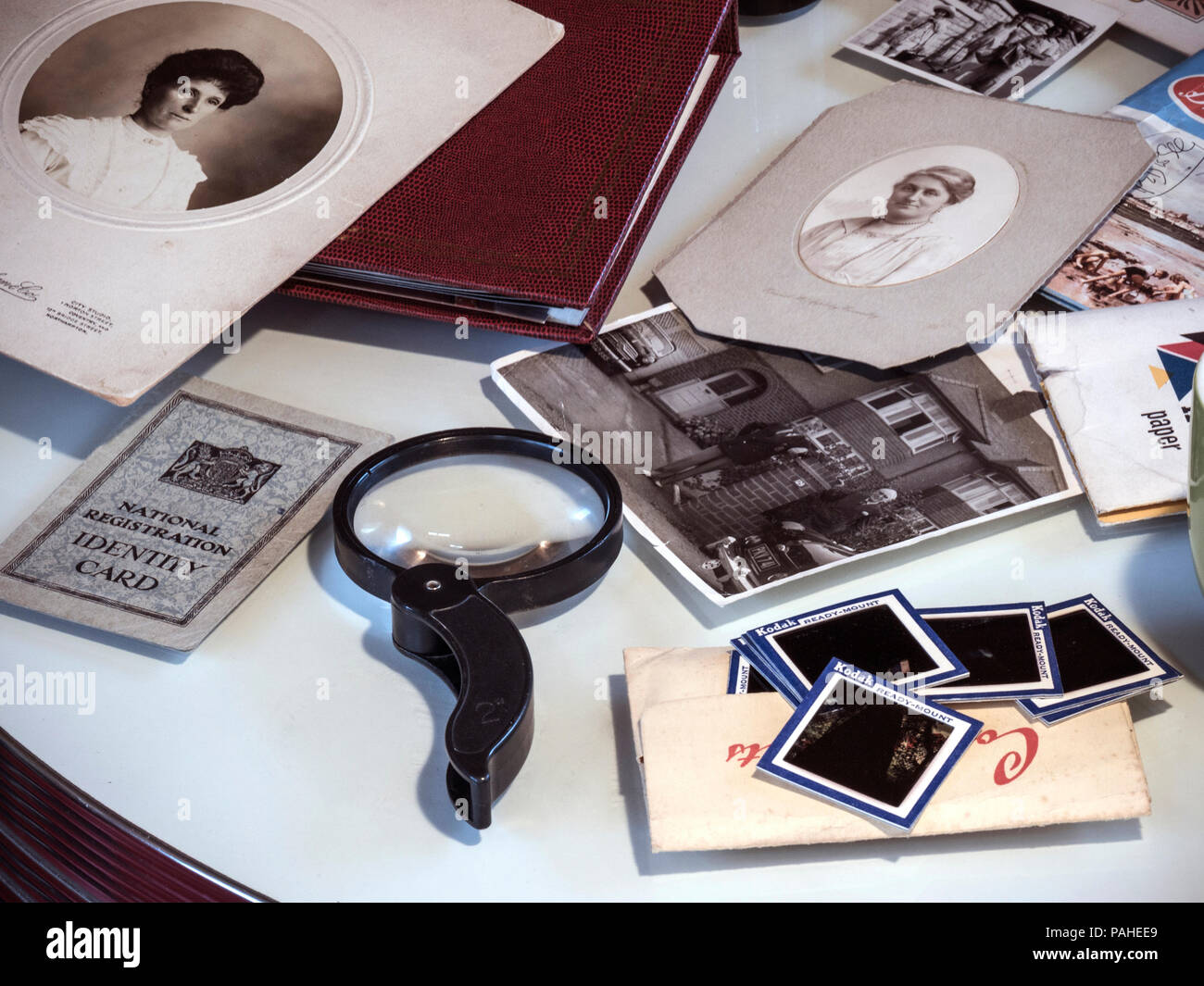 OLD FAMILY PHOTOGRAPHS sorting through historic family ephemera, documents, conventional film photography, photo albums and colour transparencies with magnifying glass - Stock Image