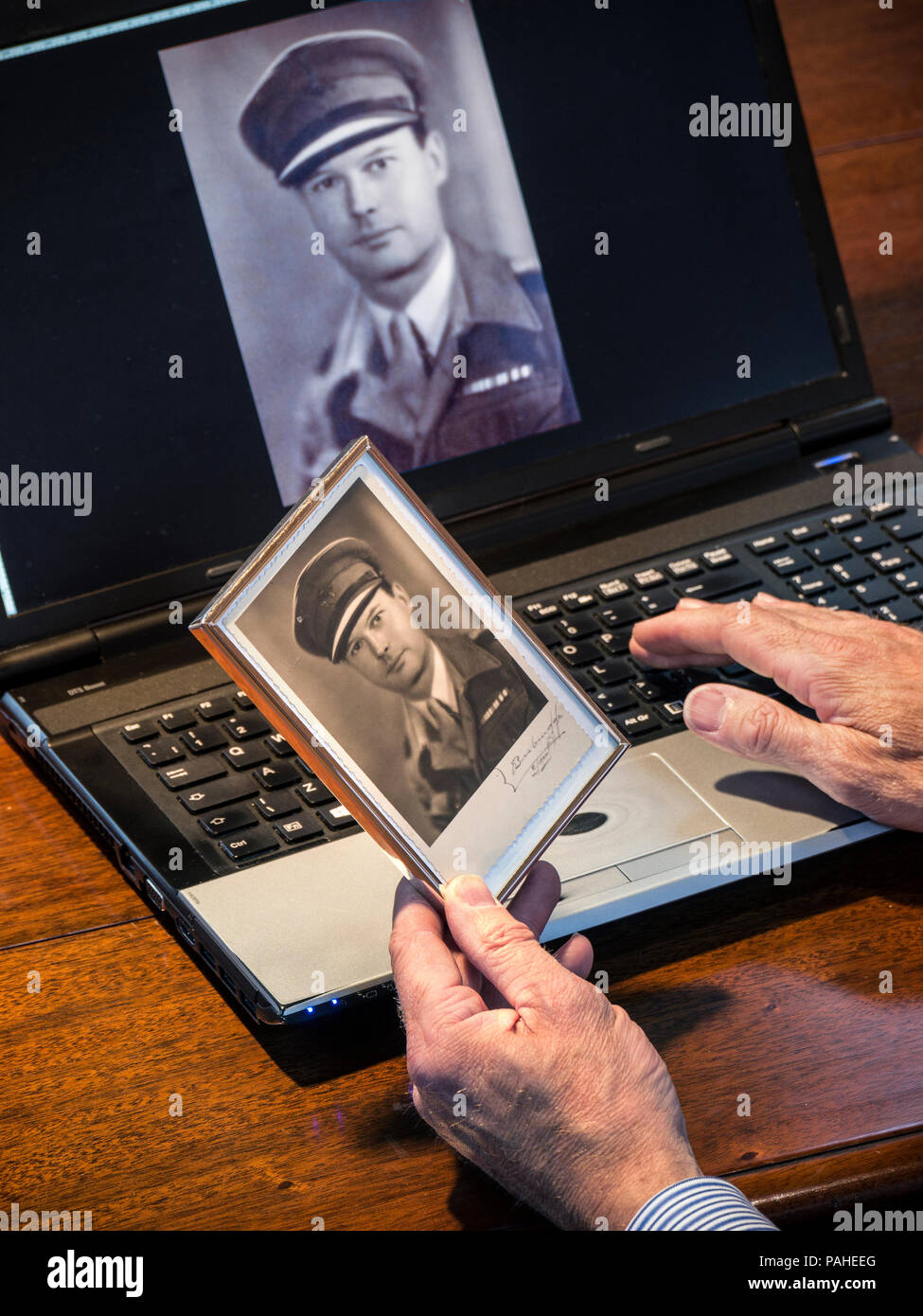 Hand holding old 1940's sepia photograph of a uniformed British Army Officer with same scanned image called up on laptop computer screen behind - Stock Image
