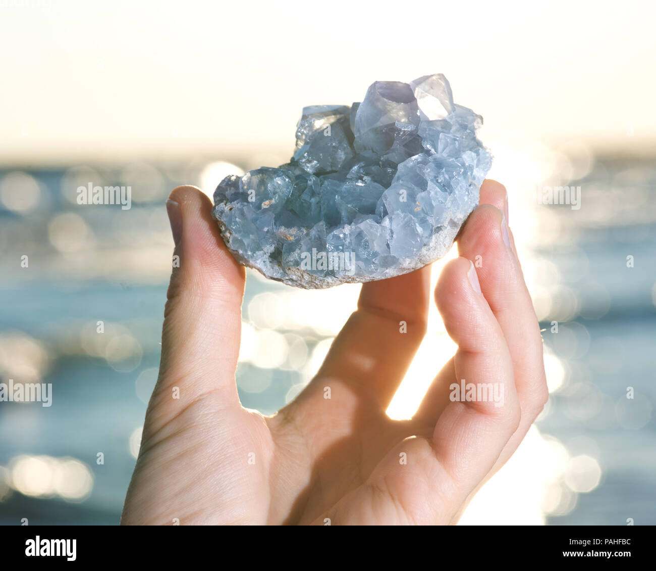 Blue Celestite cluster from Madagascar in woman's hand at sunrise in front of  the lake. - Stock Image