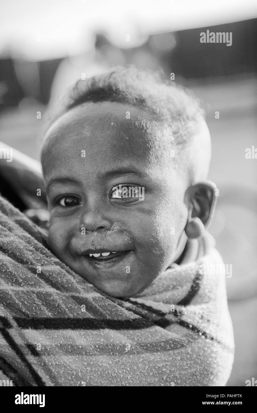 AKSUM, ETHIOPIA - SEP 30, 2011: Unidentified Ethiopian little cute happy boy is carried on his mother back in Ethiopia, Sep.30, 2011. Children in Ethi Stock Photo