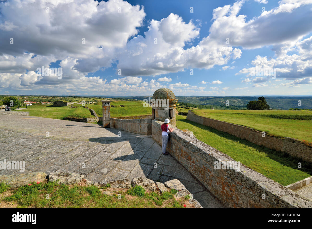 Woman enjoying view from fortress walls over a wide green land and dramatic moving clouds - Stock Image