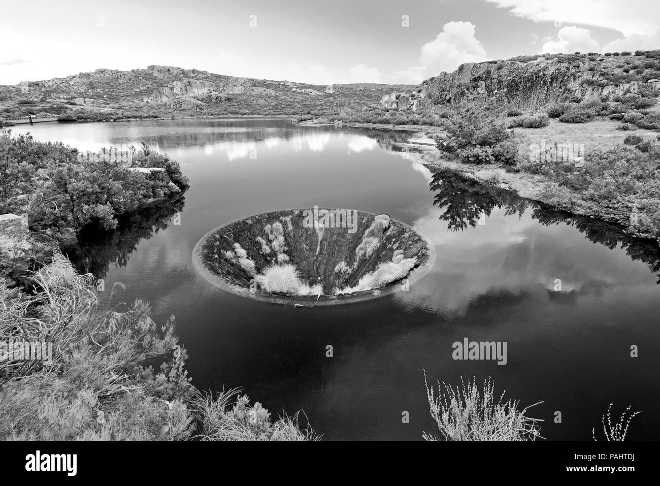 Man made funnel in the middle of a mountain lake in black and white - Stock Image