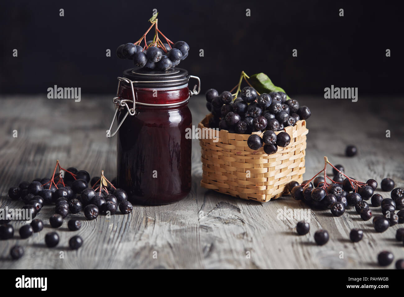 Aronia jam next to fresh berries. Homemade aronia jam in glass jar with fresh aronia berries on wooden table. - Stock Image