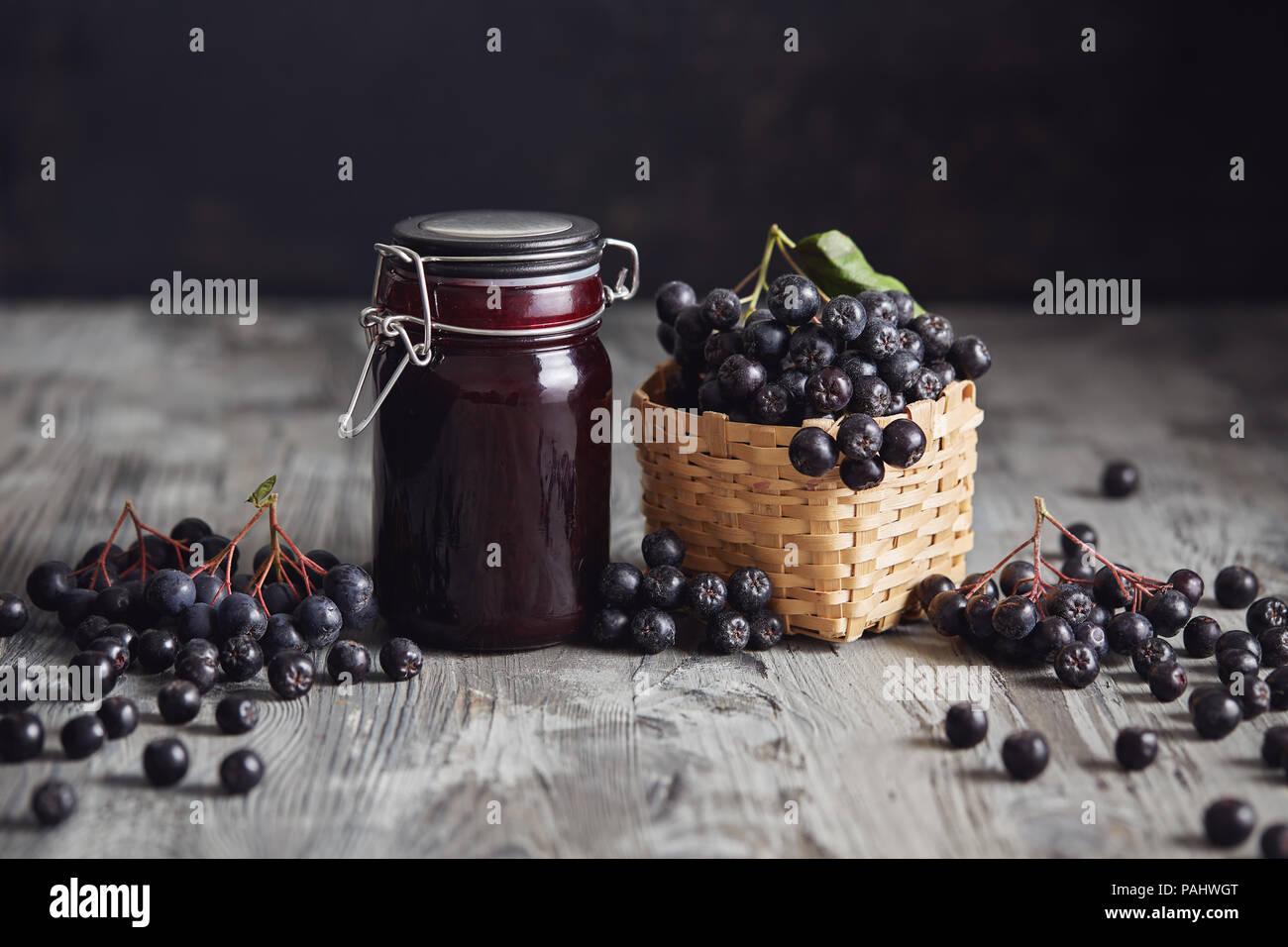 Aronia jam next to fresh berries. Homemade aronia jam in glass jar with fresh aronia berries on wooden table. - Stock Image