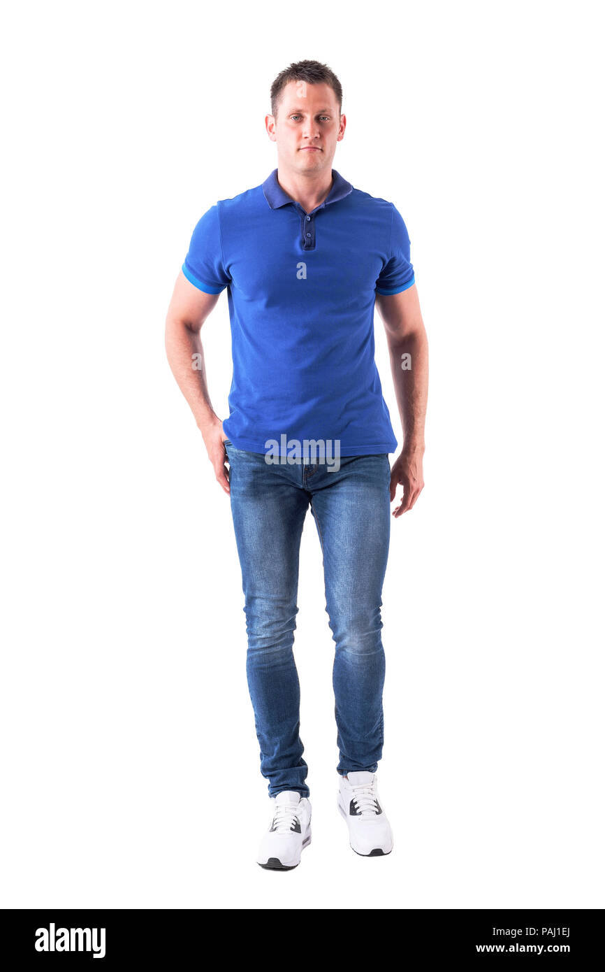Cool relaxed young adult man in polo shirt and jeans walking and looking at camera. Full body isolated on white background. - Stock Image