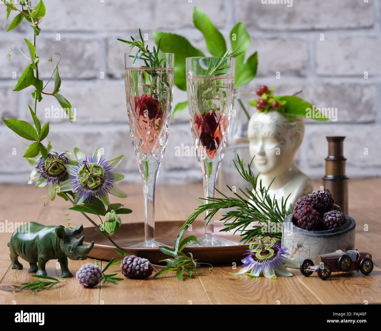 Still Life Study of curious objects including a vintage telescope, frozen blackberries, raku pottery, flower & two crystal glass flutes with prosecco - Stock Image