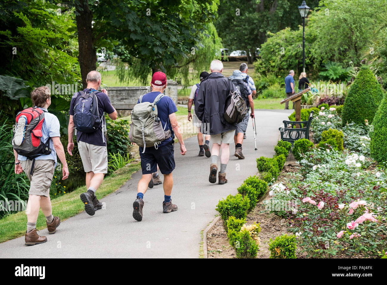 A group of walkers walking through Trenance Park in Newquay Cornwall. - Stock Image