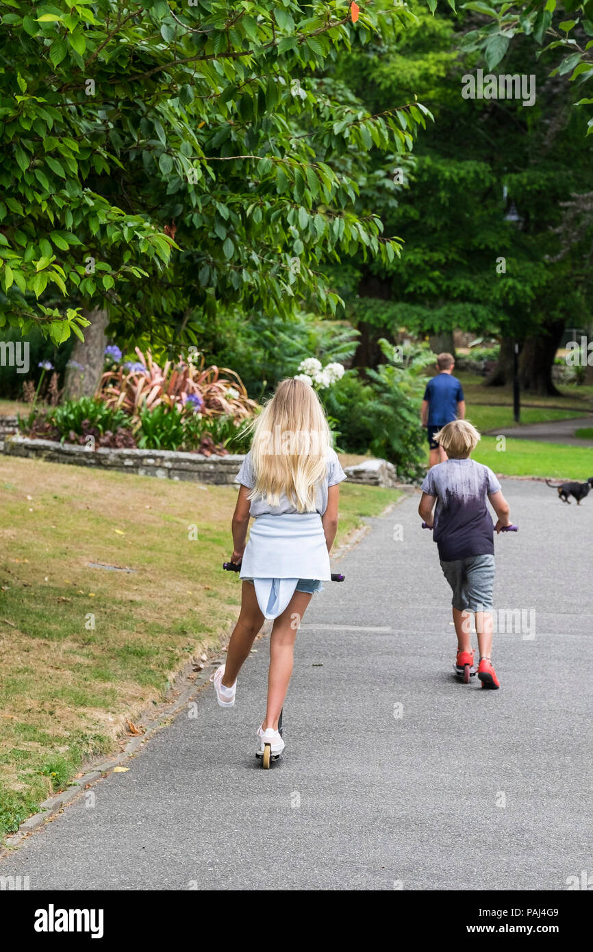 Children on scooters in Trenance Garden in Newquay Cornwall. - Stock Image