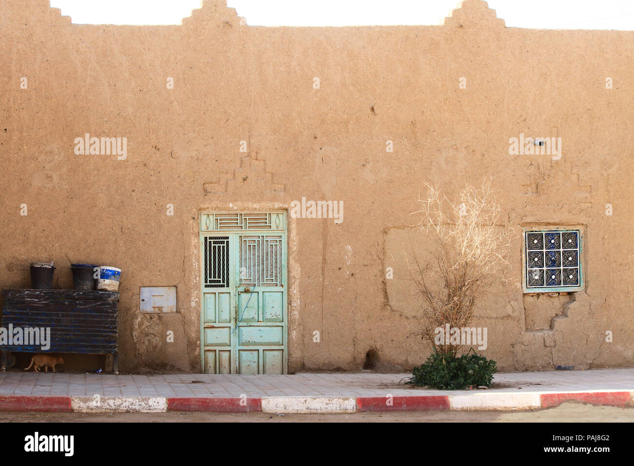 Village traditional house with pastel green steel doors on sunny day. Sahara Desert. Morocco, Africa. - Stock Image