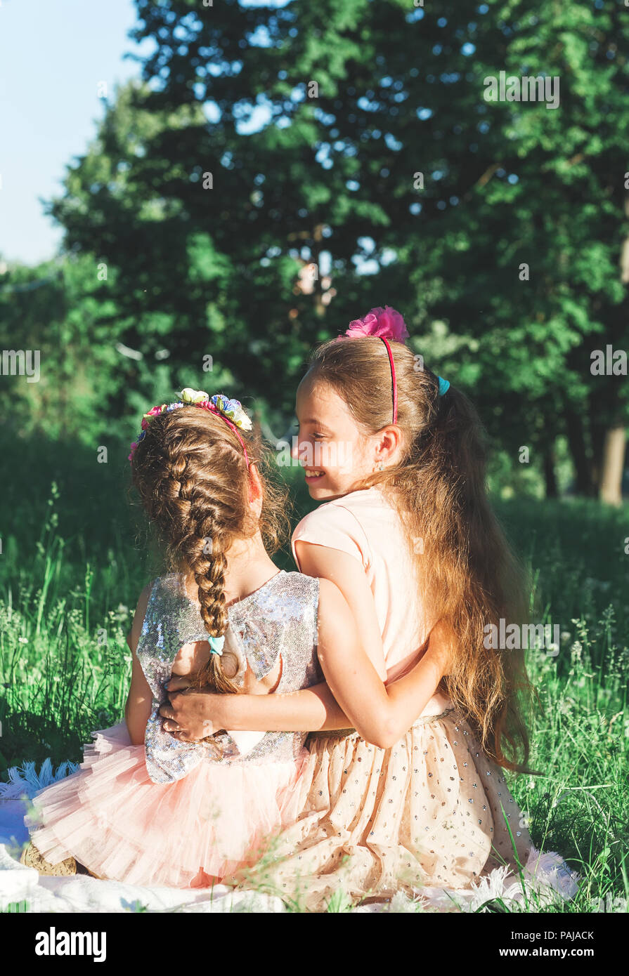 Toned portrait of Two Happy little girls embracing  and spending time at sunny summer park - Stock Image