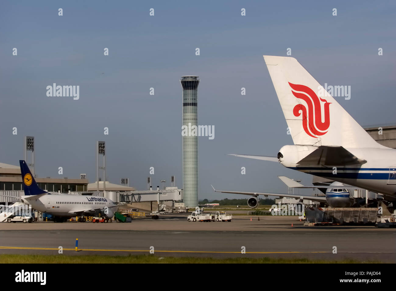 Air China tail with logo and B747-400 winglet with an A340 wing & engines, Lufthansa 737 parked and control-tower behind Stock Photo