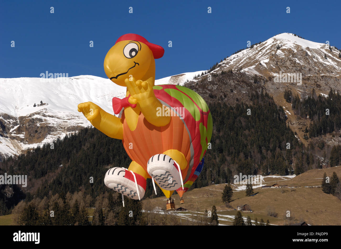 a Cameron SS-120 Turtle special shape hot-air balloon flying with trees, snow and mountains behind Stock Photo