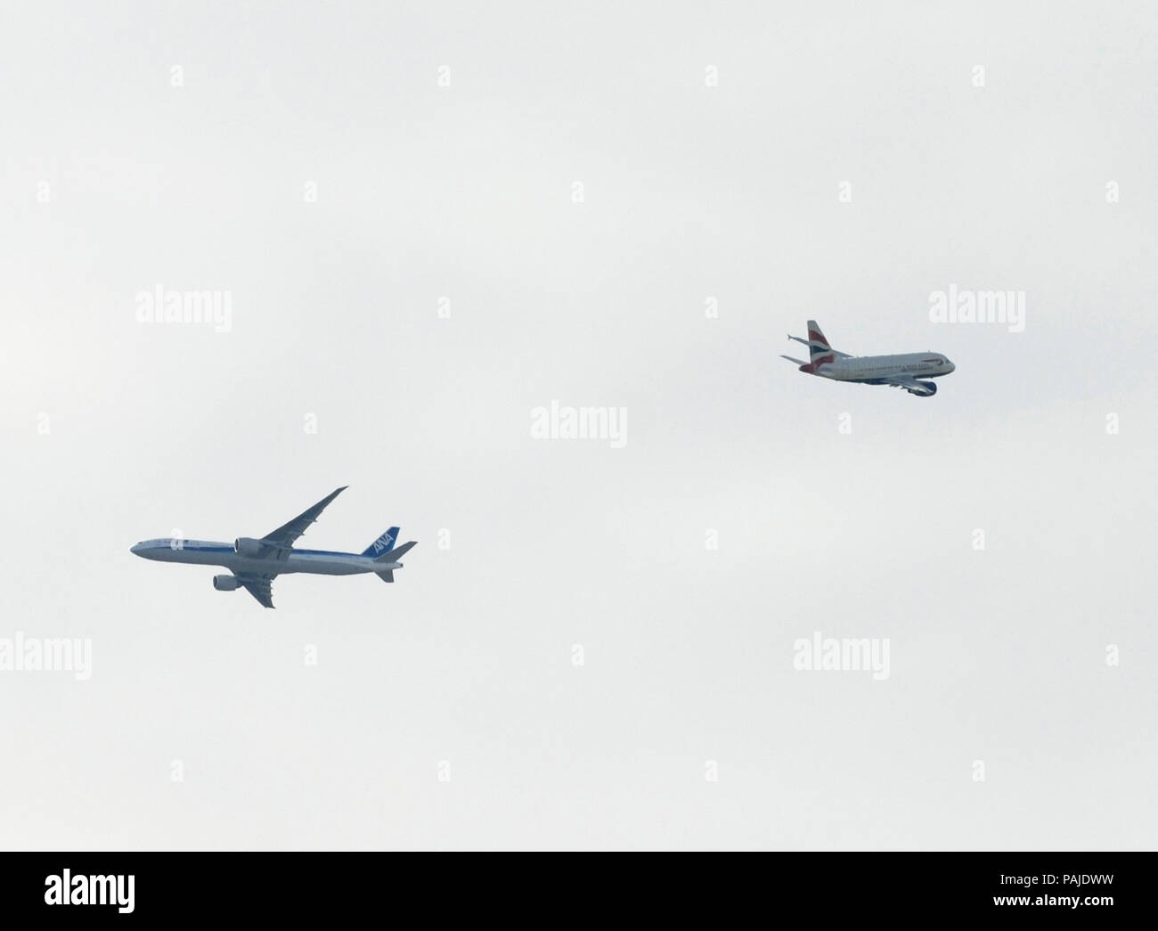 British Airways Airbus A318-100 climbing enroute and an ANA Boeing 777-200 flying enroute - Stock Image