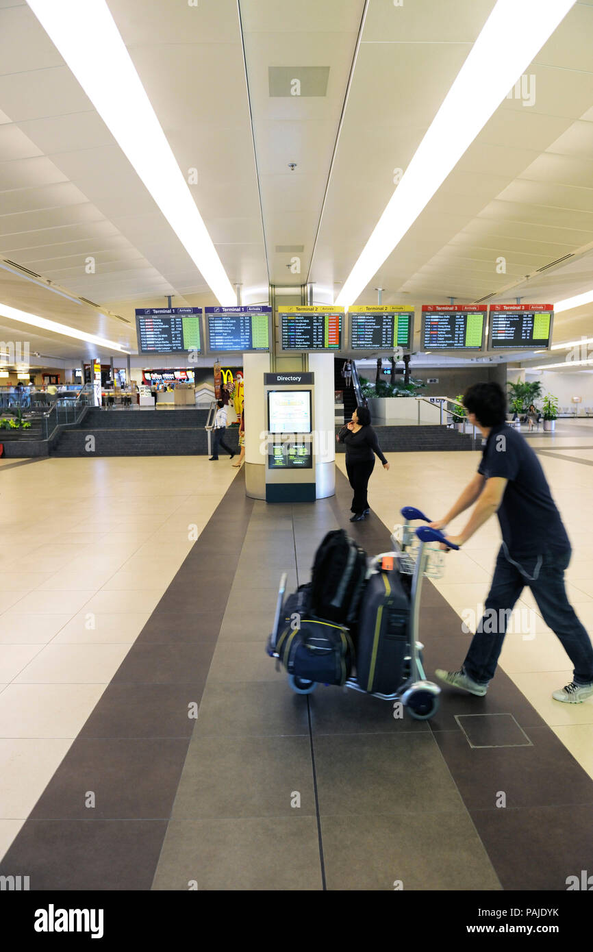 passenger with bags and trolley with flight arrivals information screens in Singapore Changi Terminal2 Stock Photo