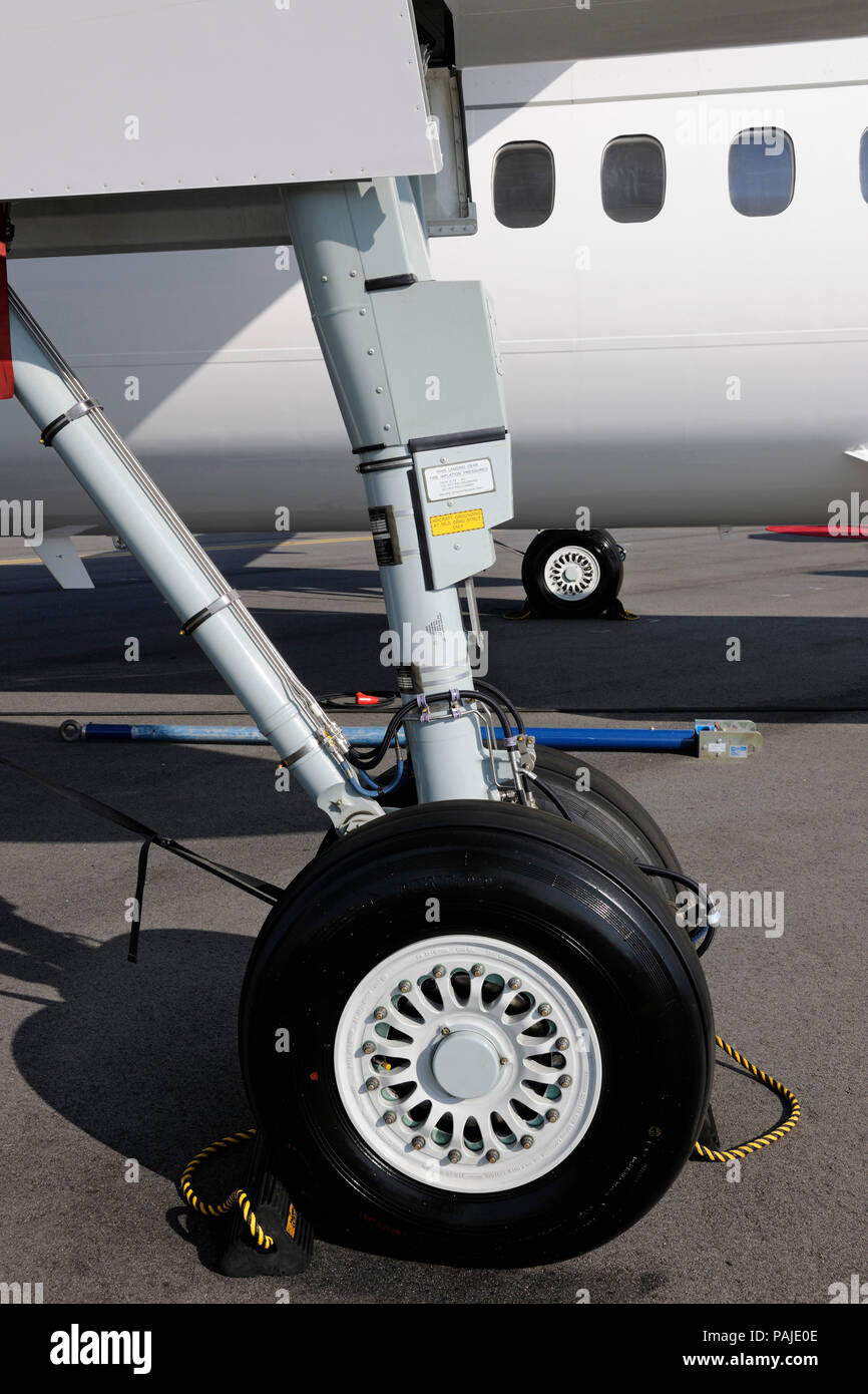 chock and mainwheel undercarriage of AirBaltic Bombardier DHC-8 Q400 Next Generation parked in the static-display at the Singapore-Airshow 2010 - Stock Image