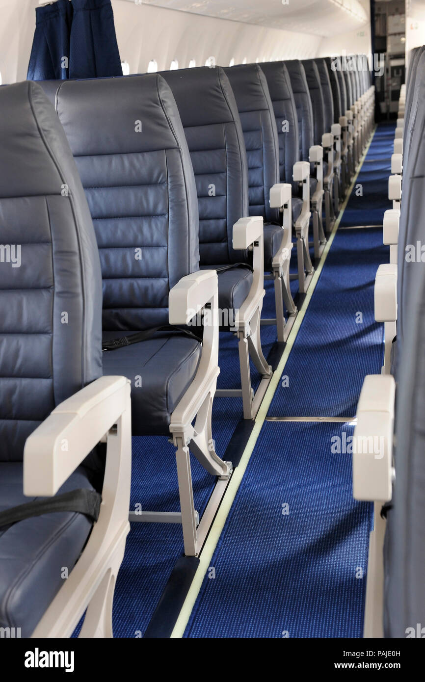 aisle and armrests of empty passenger cabin seats on AirBaltic Bombardier DHC-8 Q400 Next Generation parked in the static-display at the Singapore-Air - Stock Image