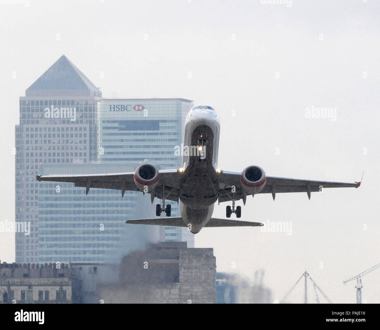 Baboo Embraer 190 climbing out after take-off with Canary Wharf behind Stock Photo