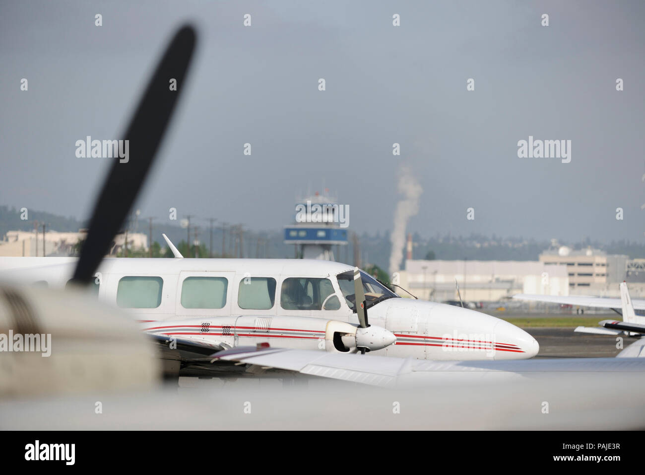 windows of Aeroflight Executive Services Piper PA-31-350 Navajo Chieftain parked and air-traffic control-tower behind Stock Photo
