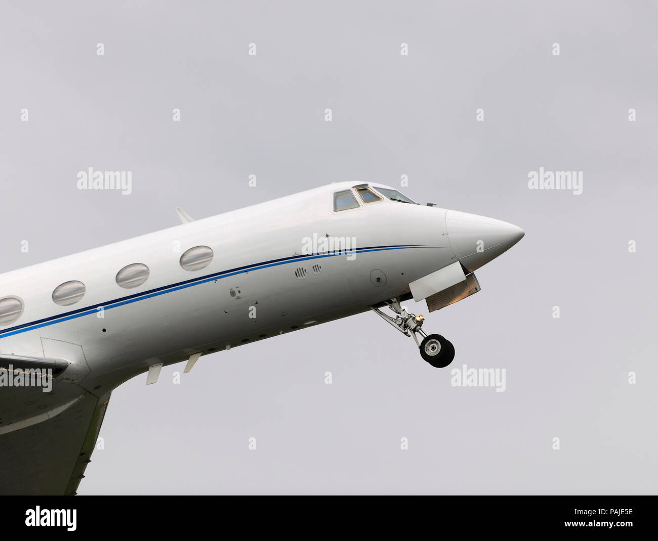 nose of Grumman G-1159 Gulfstream 2 / II climbing out after take-off with undercarriage retracting Stock Photo