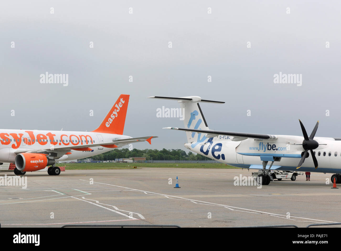 Flybe Bombardier DHC-8 Q400 parked with easyJet Airbus A319 taxiing behind - Stock Image