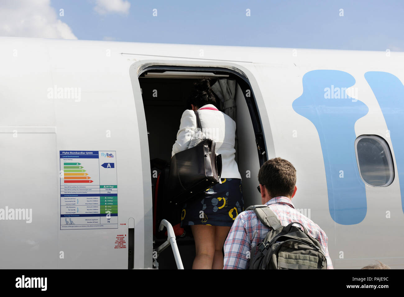 passengers with carry-on bags boarding a Flybe Bombardier DHC-8 Q400 parked Stock Photo