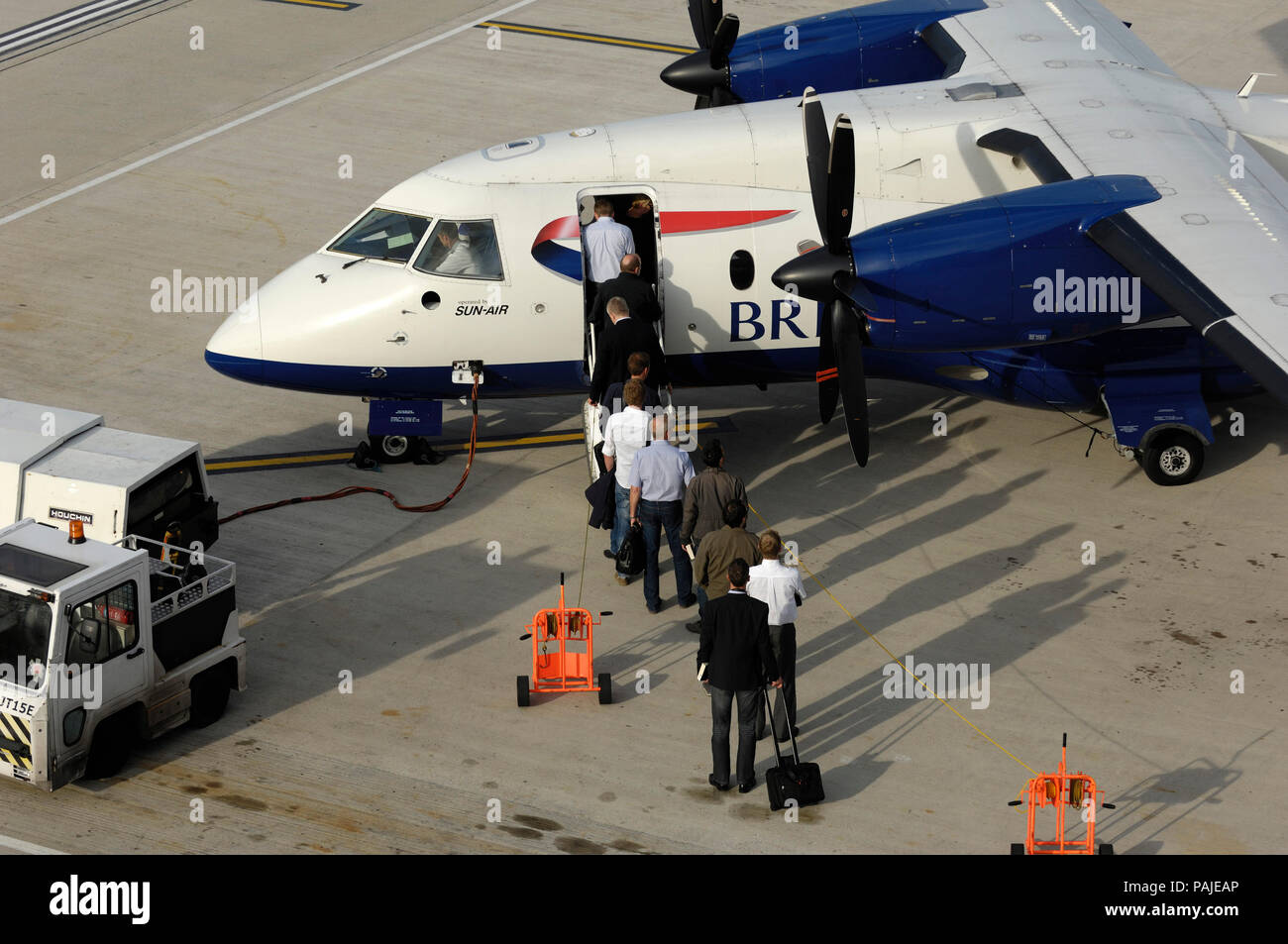 passengers with carry-on bags boarding a British Airways - Sun Air Dornier Do-328-100 parked at London City - Stock Image