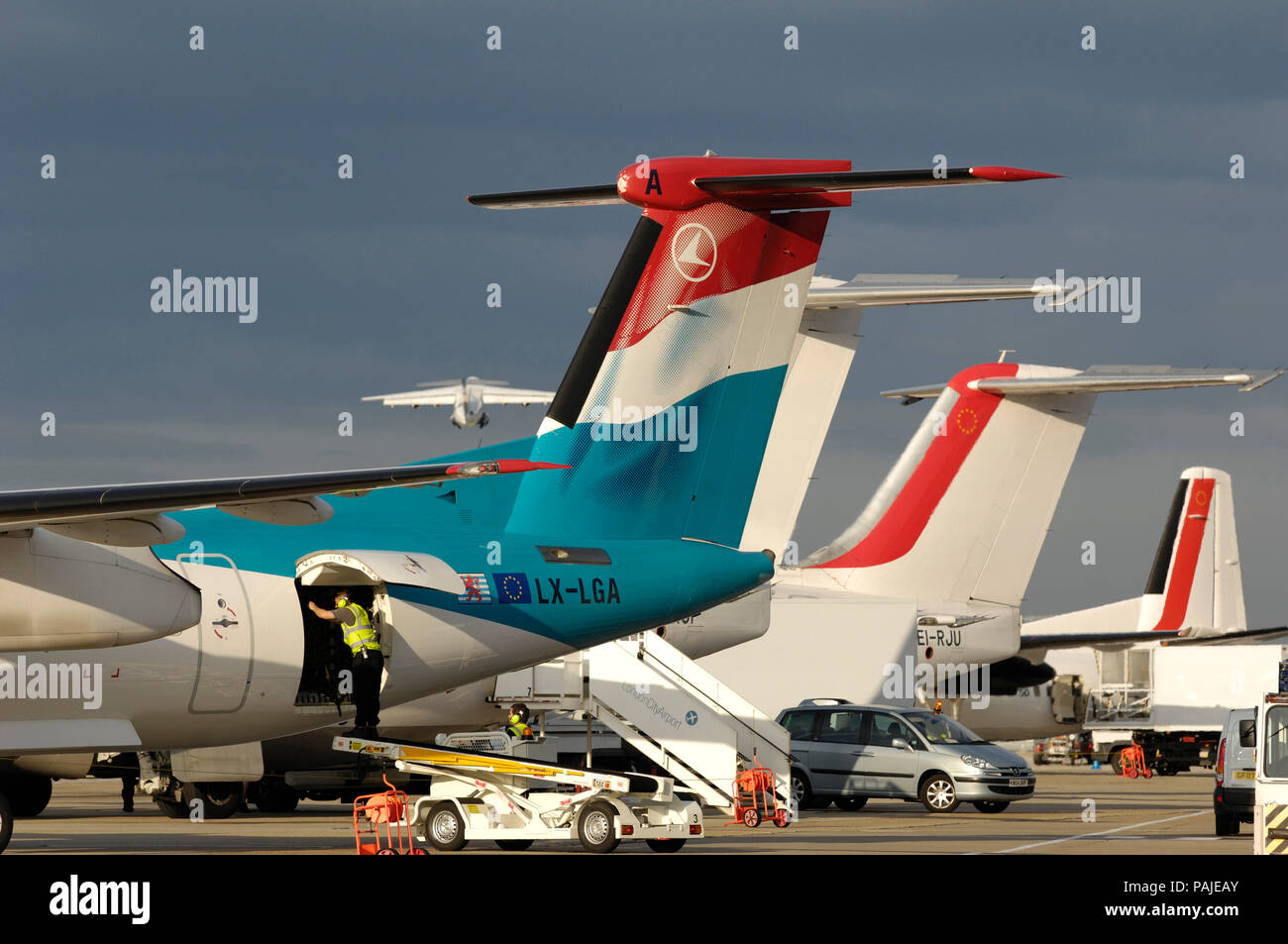 tail-fins of Luxair Bombardier DHC-8 Dash 8-400 Q400 with CityJet BAE 146s and Fokker F-50 parked at London City - Stock Image