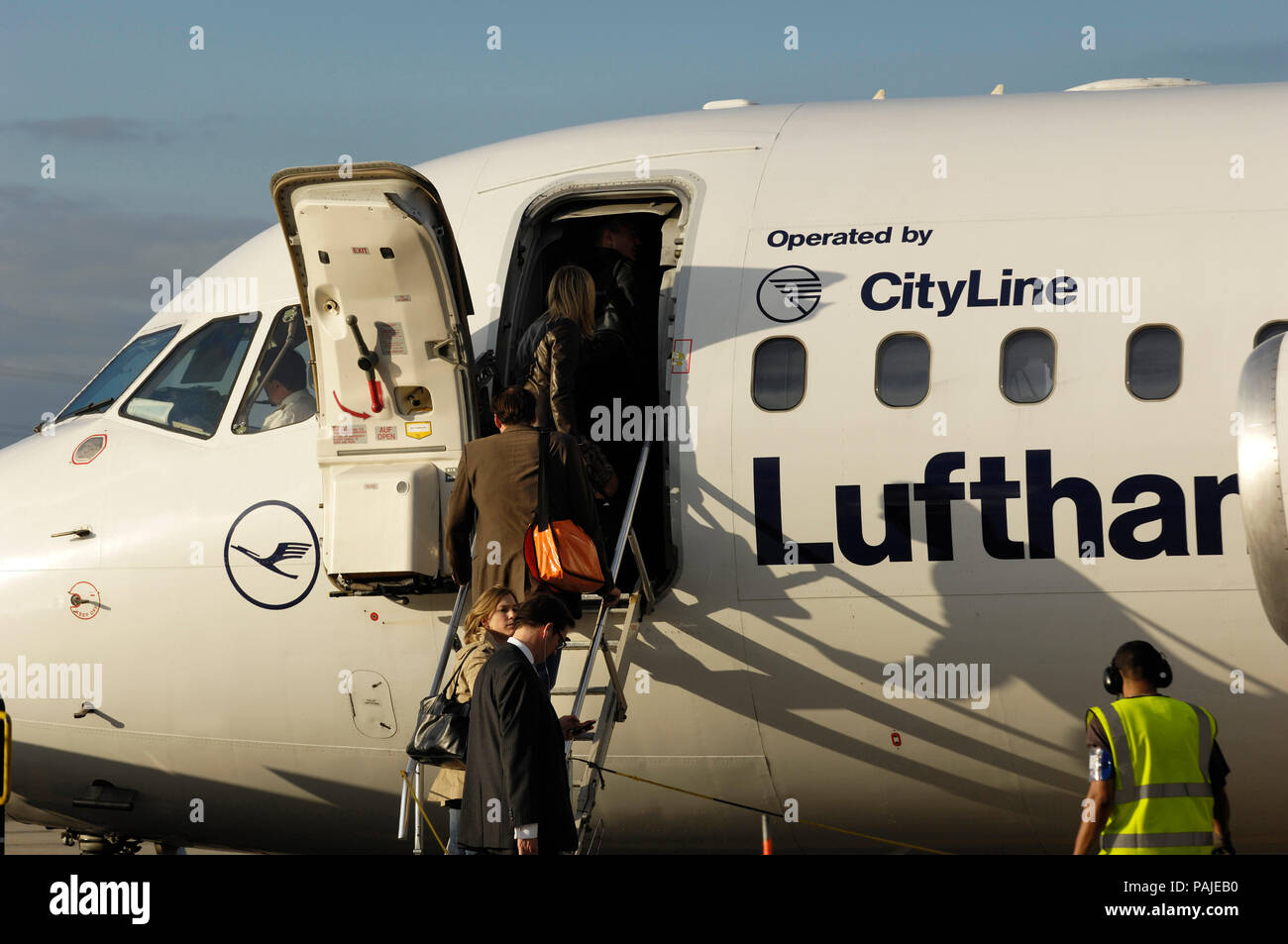 passengers with carry-on bags boarding a Lufthansa Regional BAE 146 Avro RJ-85 parked at London City Stock Photo