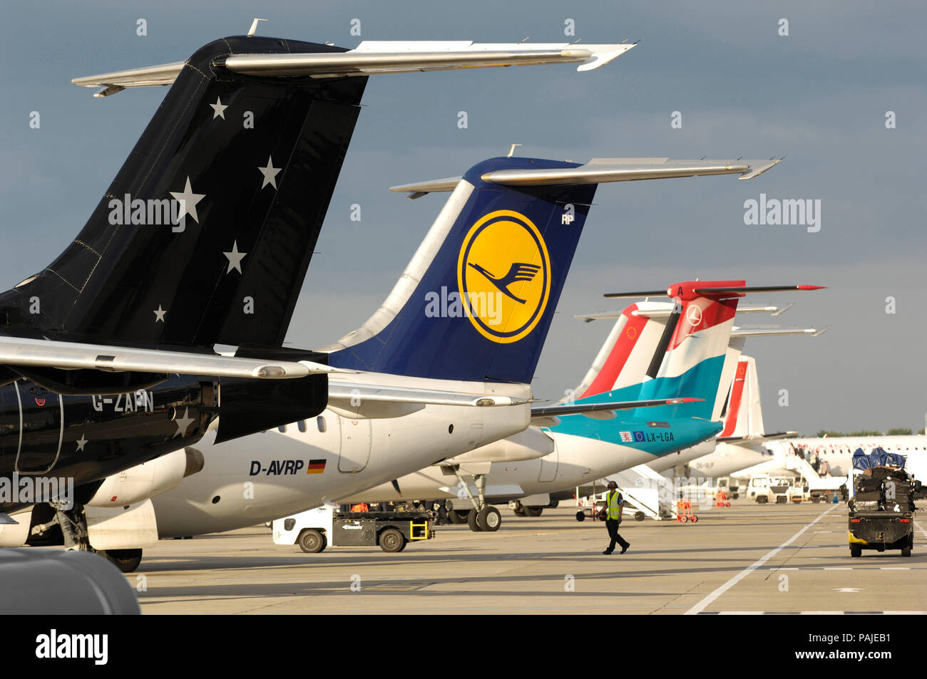 tail-fins of Titan Airways BAE 146-200 QC with Lufthansa Regional BAE 146 RJ-85 and Luxair Bombardier DHC-8 Q400 parked behind at London City - Stock Image